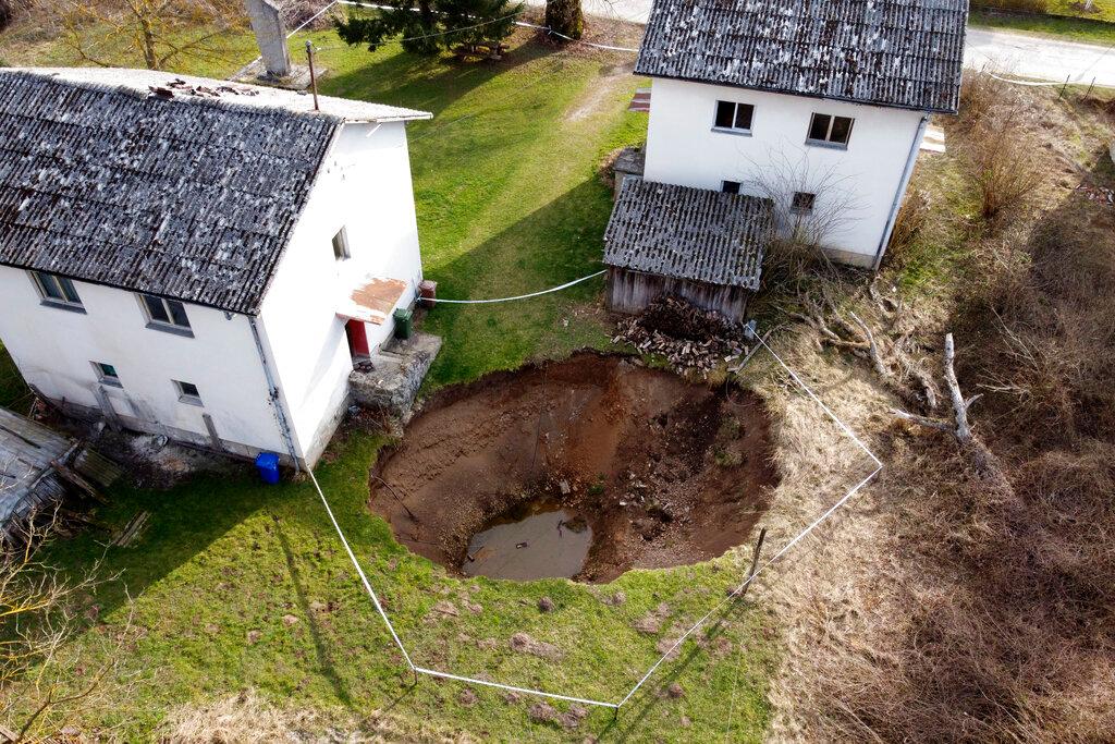 Cette photo aérienne montre un gouffre dans le village de Mececani, au centre de la Croatie, le jeudi 4 mars 2021. Une région du centre de la Croatie à environ 40 kilomètres au sud-ouest de la capitale Zagreb est parsemée de trous ronds de toutes tailles, apparus après Séisme de magnitude 6,4 en décembre qui a tué sept personnes et causé des destructions généralisées.  Les scientifiques affluent vers Mecencani et d'autres villages de la région peu peuplée pour l'observation et l'étude.