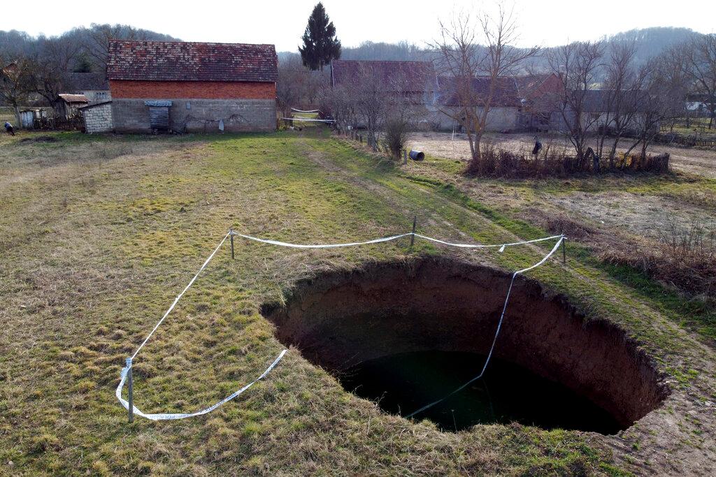 Cette photo aérienne montre un gouffre dans le village de Mececani, dans le centre de la Croatie, le jeudi 4 mars 2021. Une région du centre de la Croatie à environ 40 kilomètres au sud-ouest de la capitale Zagreb est parsemée de trous ronds de toutes tailles, apparus après Séisme de magnitude 6,4 en décembre qui a tué sept personnes et causé des destructions généralisées.  Les scientifiques affluent vers Mecencani et d'autres villages de la région peu peuplée pour l'observation et l'étude.